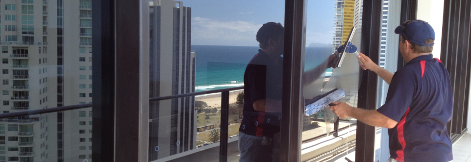 Cleaning balcony glass on a high rise building